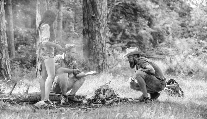 Add some wood to fire. Friends hang out near bonfire picnic. Company youth camping forest prepare bonfire for picnic royalty free stock photography
