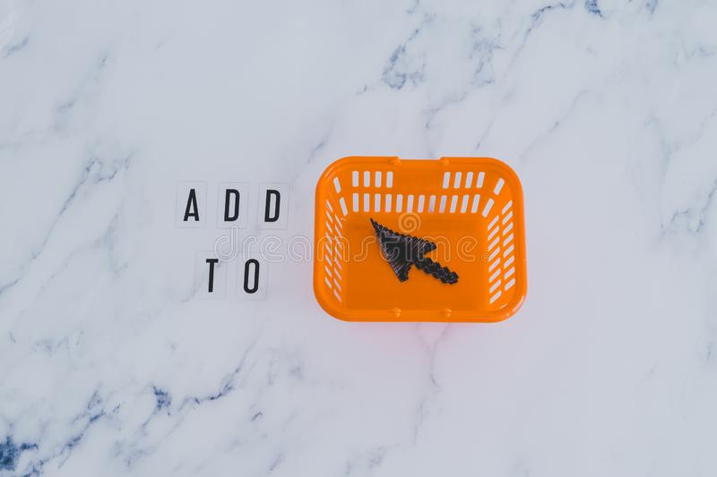 Add to cart concept, message on desk with shopping basket and mouse pointer icon inside. Add to cart and online shopping concept, message on desk with shopping royalty free stock image