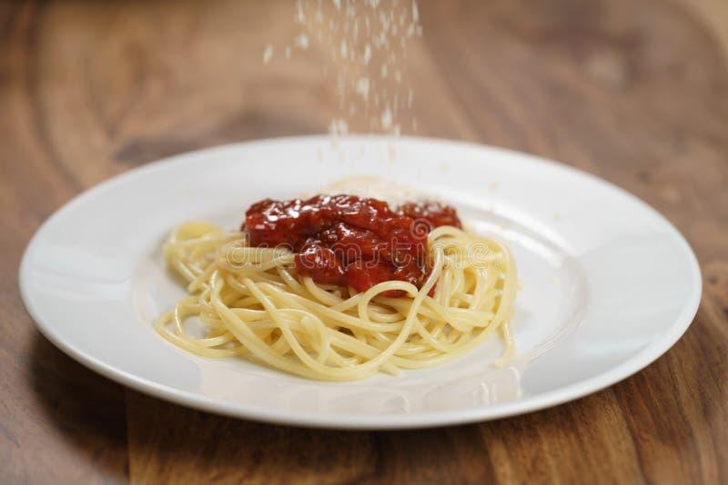 Add zerrieb Parmesankäse auf Spaghettis Bewohner von Bolognese lizenzfreie stockfotos