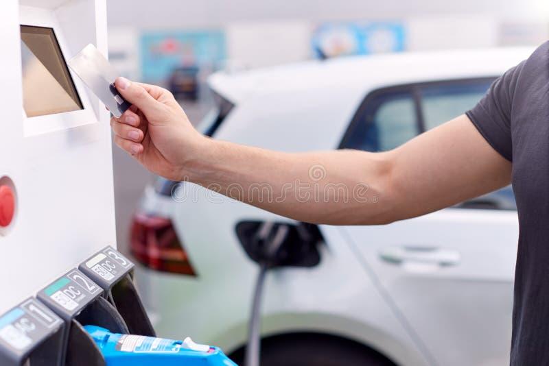 Addebitrice Di Veicoli Elettrici Che Pagano Per L'Energia Con Carta Di Credito Alla Stazione Di Carica immagine stock