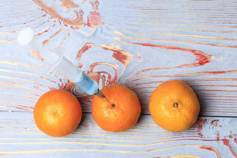 Added mandarin with a syringe. Background wooden in the old stele. in a syringe blue liquid. Chemical experiments in the food. Industry stock photo