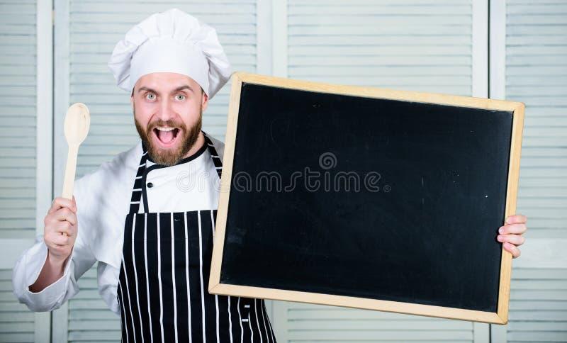 Addestramento culinario Classe matrice d'istruzione del capo cuoco nella cottura della scuola Uomo che tiene cucchiaio e lavagna  fotografia stock libera da diritti