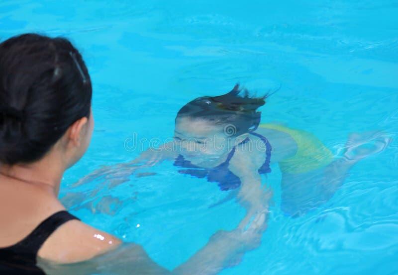 Addestramento d'immersione della bambina con la madre allo stagno di acqua fotografie stock