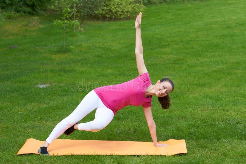 Addestramento dai capelli della donna di Brown dei muscoli laterali del corpo nell'equilibrio su una gamba e su una mano immagine stock