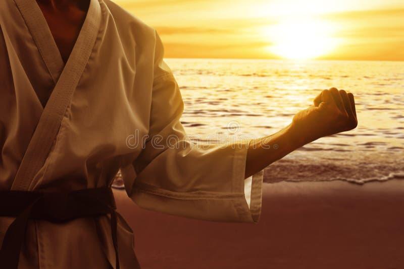 Addestramento del combattente di arti marziali sulla spiaggia fotografia stock