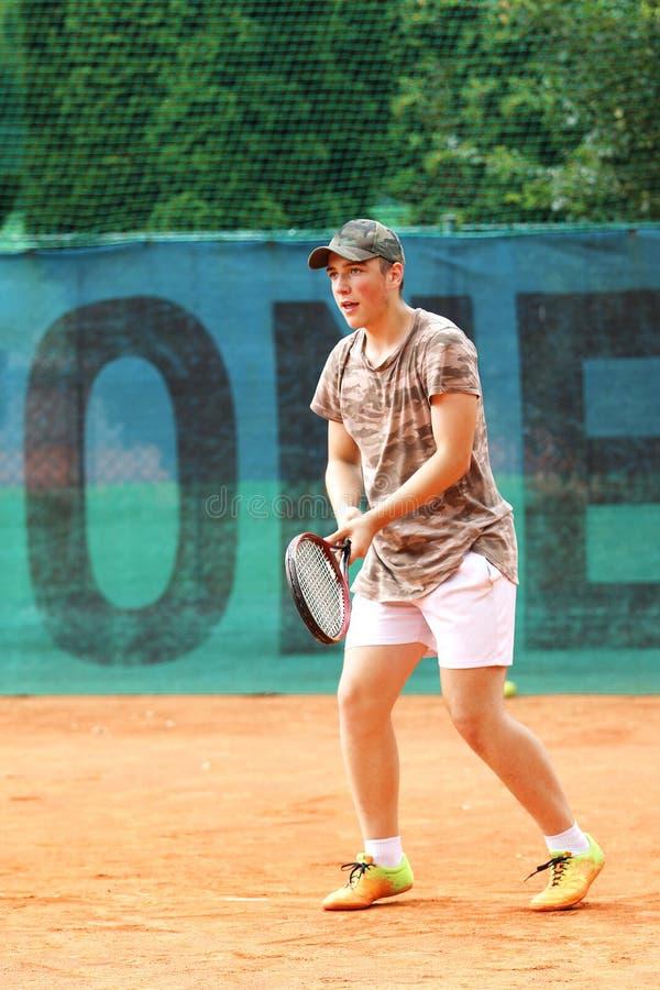 Addestramento del ragazzo da giocar a tennise sulla corte che ha cappuccio immagini stock libere da diritti