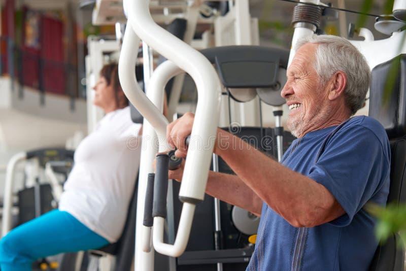Addestramento dell'uomo senior sulla macchina al centro di forma fisica immagini stock