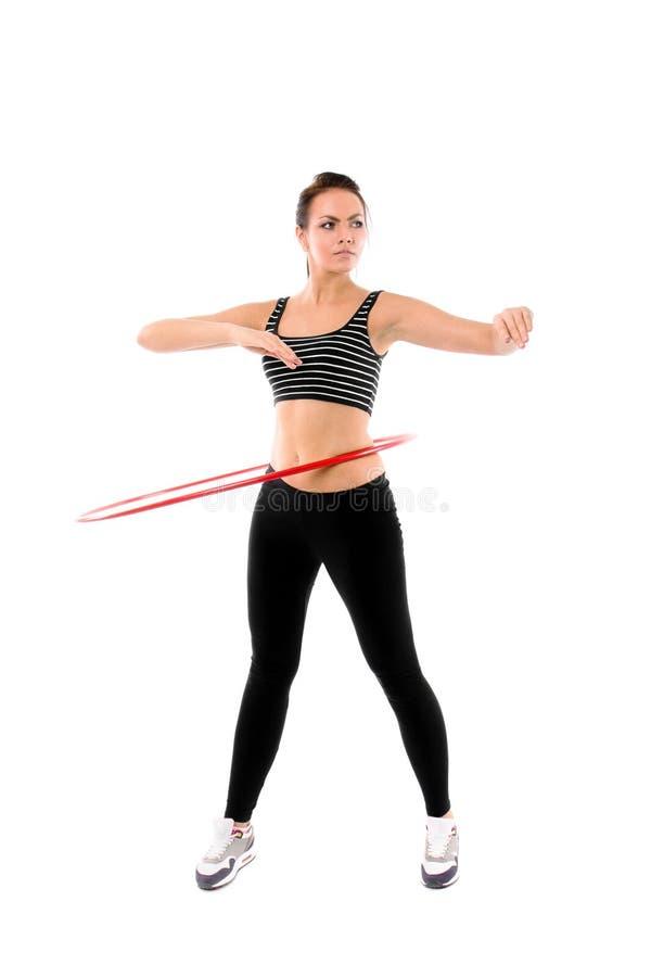 Addestramento della donna con il hula-hoop isolato su bianco fotografia stock libera da diritti