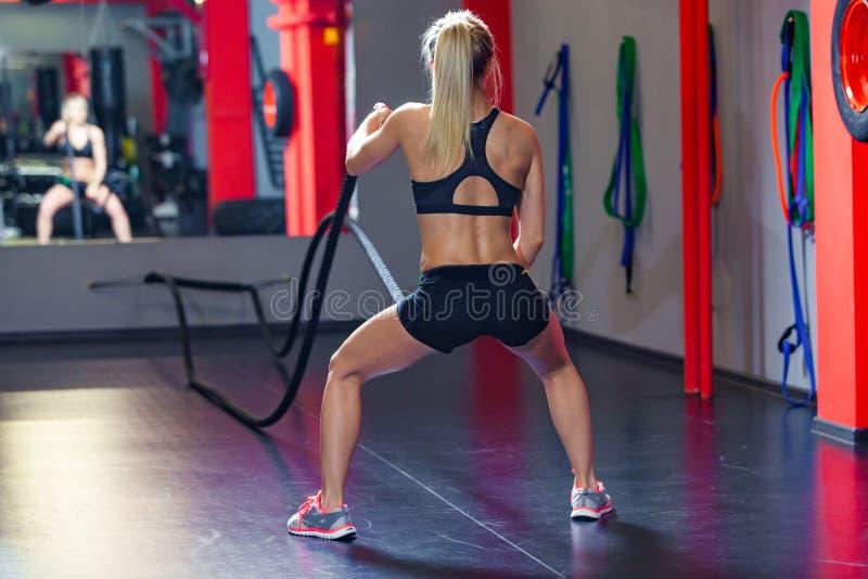 Addestramento della donna con la corda di battaglia nella palestra adatta dell'incrocio Vista posteriore fotografia stock libera da diritti