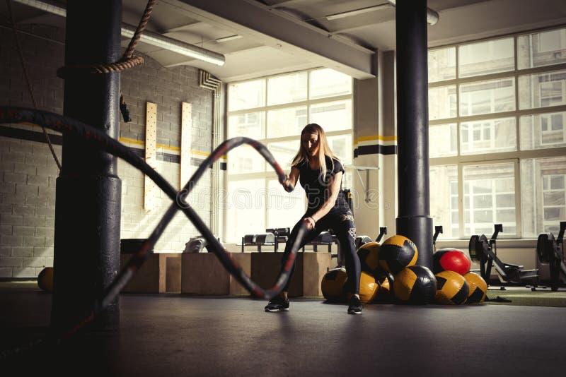 Addestramento della donna con le corde di battaglia in palestra fotografia stock