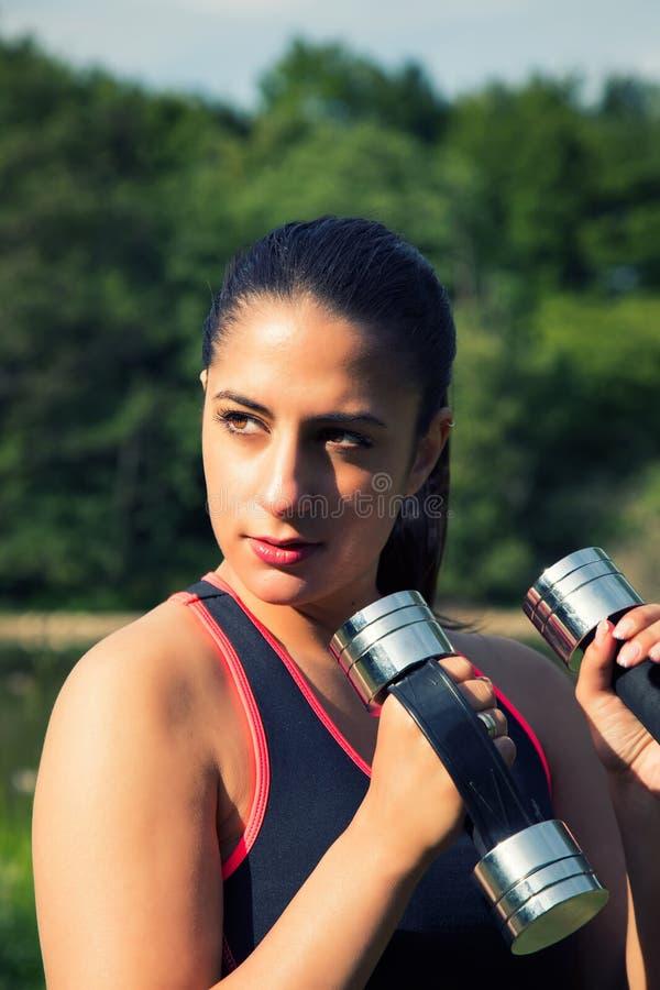 Addestramento della giovane donna con il peso in natura fotografie stock