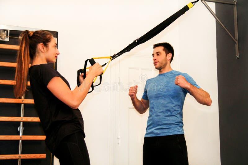 Addestramento della sportiva con la banda di resistenza del trx con l'istruttore immagini stock