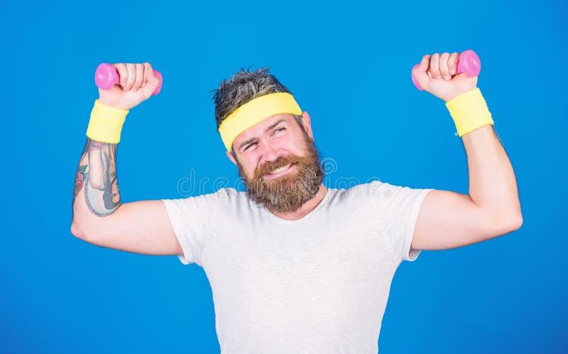 Addestramento dello sportivo con il fondo blu delle teste di legno Migliori i vostri muscoli Usi i pesi o le teste di legno Atlet immagine stock