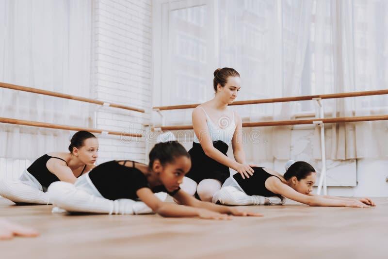 Addestramento di balletto delle ragazze sul pavimento con l'insegnante immagine stock libera da diritti