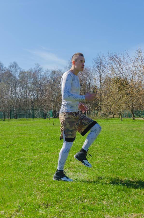 Addestramento maschio di estate degli abiti sportivi nel parco immagine stock