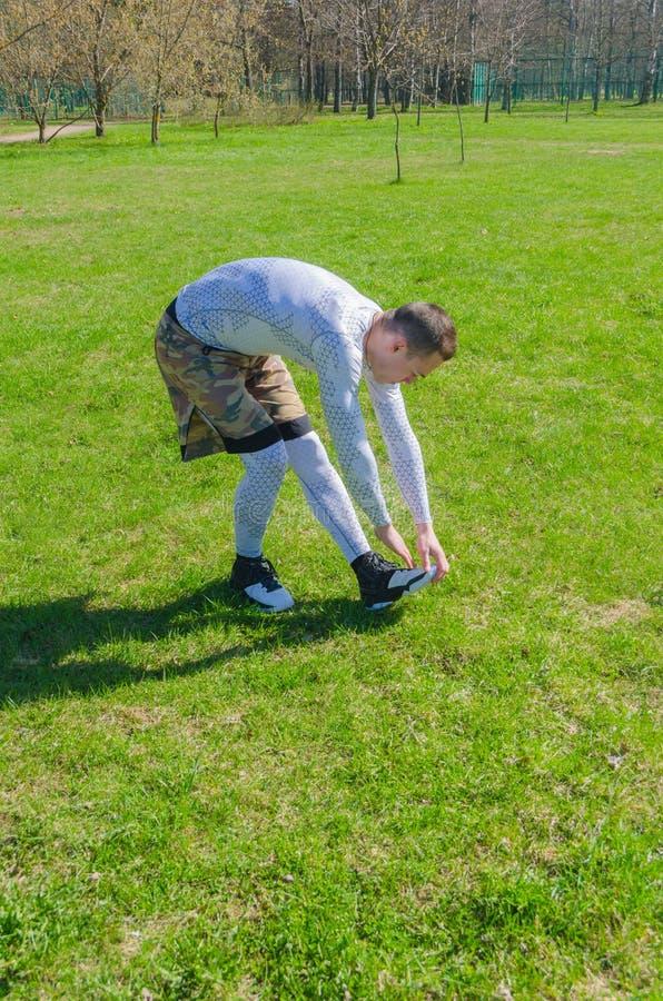 Addestramento maschio di estate degli abiti sportivi nel parco fotografie stock