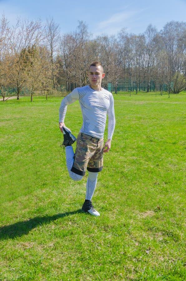 Addestramento maschio di estate degli abiti sportivi nel parco fotografia stock