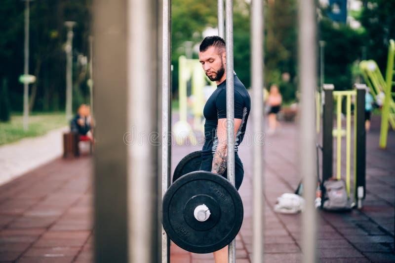 Addestramento muscolare dell'uomo nel parco Peso massimo che solleva nel parco con i dumbells fotografia stock libera da diritti