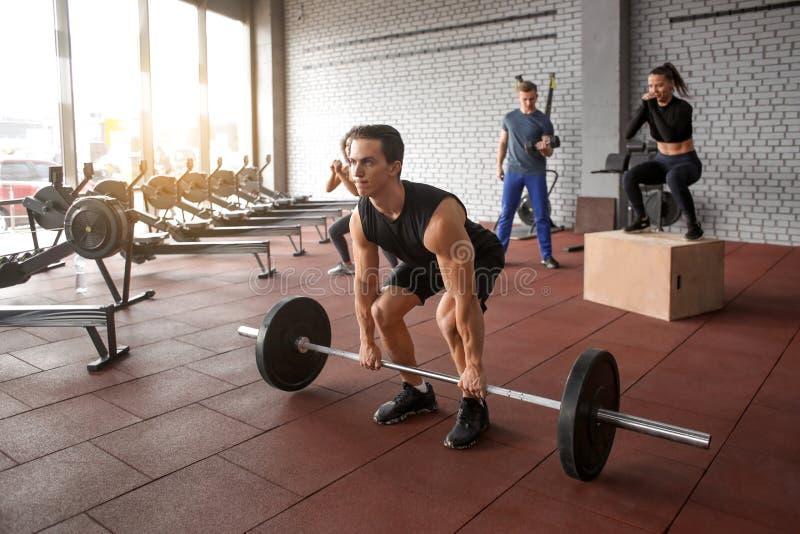 Addestramento sportivo dell'uomo nella stanza di peso immagine stock libera da diritti