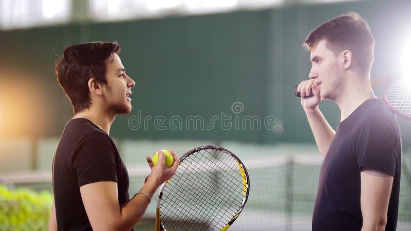 Addestramento sul campo da tennis Conversazione dei giocatori dei giovani fotografie stock