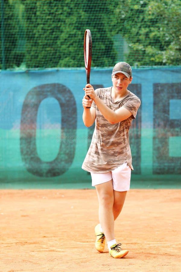 Addestramento teenager del ragazzo sul campo da tennis immagine stock libera da diritti