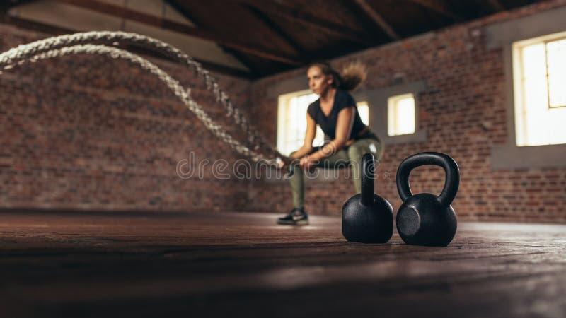 Addestramento trasversale femminile al club di forma fisica fotografia stock