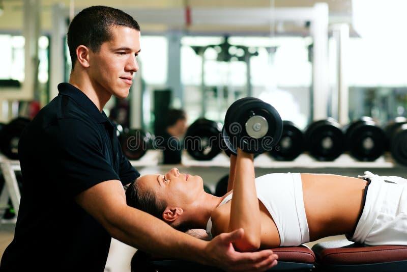 Addestratore personale in ginnastica fotografia stock