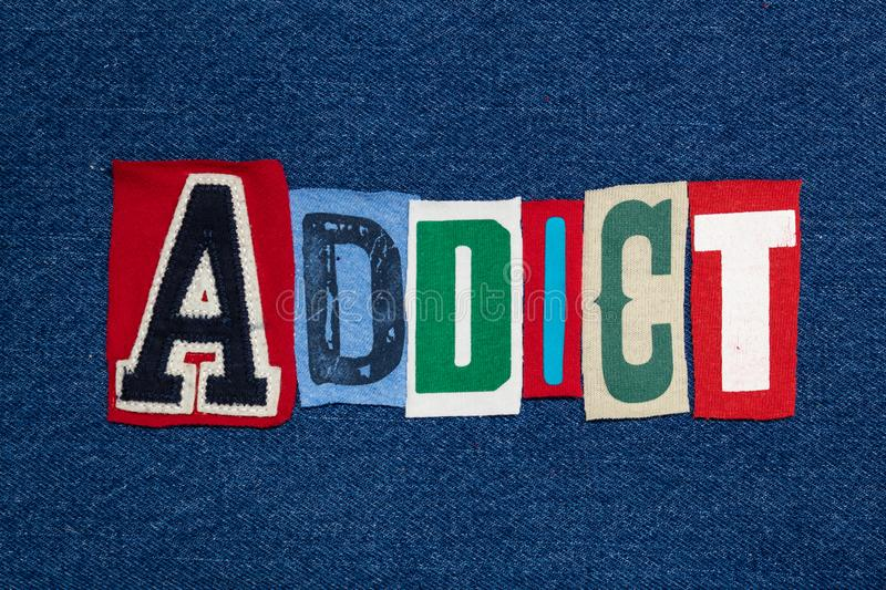ADDICT text word collage, colorful fabric on blue denim, health and addiction concept stock photos