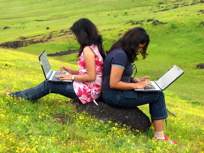 Addicted. Two teenagers addicted to chatting on their wireless connection with their laptops in the wild royalty free stock photo