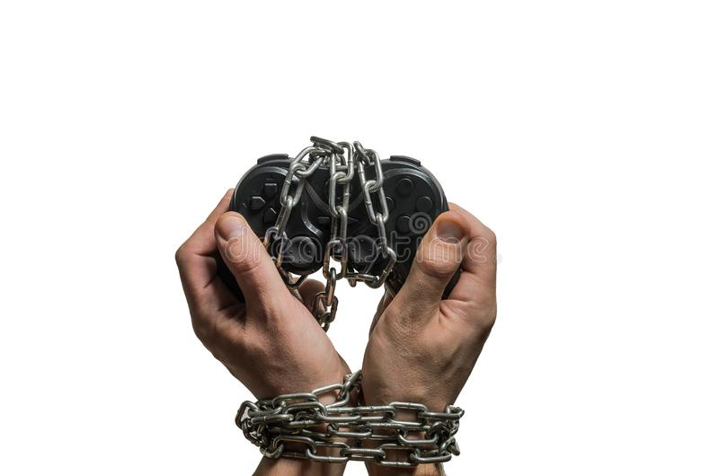 Addicted gaming player`s hands with joystick chained in chains isolated on white background.  stock photography