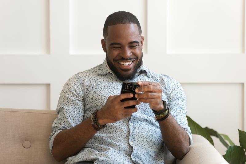 Addicted happy smiling african american guy using mobile phone. royalty free stock image
