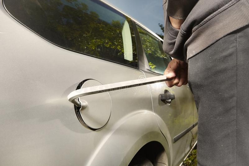 Hooded man trying to steal car fuel on public park place. Addicted man in black hooded shirt stealing car stock photo