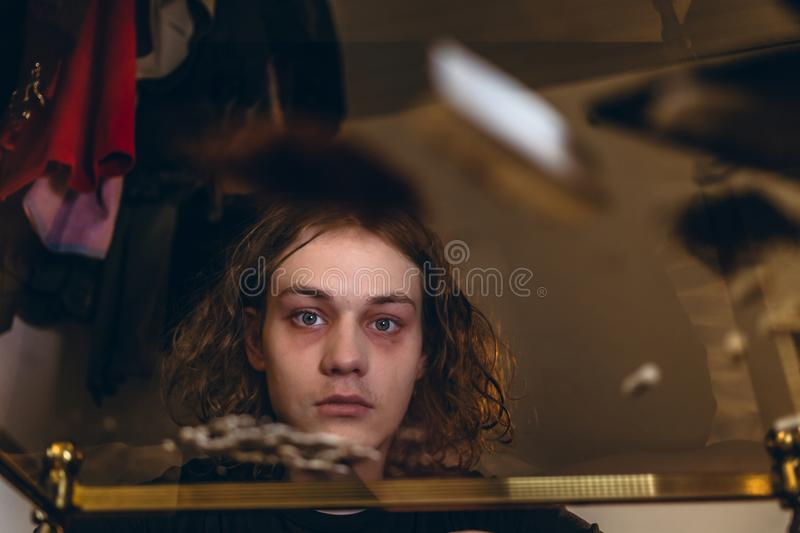 Addicted teenage boy experiencing psychotropic effects caused by. Low-angle view portrait of an addicted teenage boy staring while experiencing psychotropic stock photo