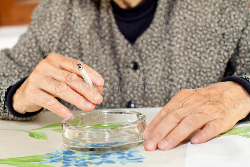 Addicted to nicotine. Elderly woman addicted to nicotine and smoking stock photo