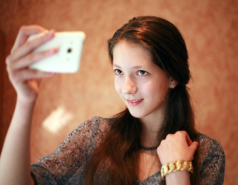 Addicted to selfies. Beautiful white haired teen girl dressed in a blue blouse her mother's necklace and a gold bracelet. Girl smiling and making selfie on my stock image