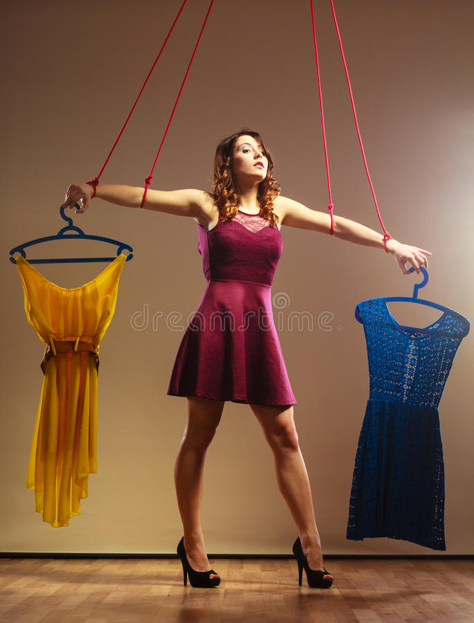 Addicted to shopping woman girl marionette with clothes stock photography