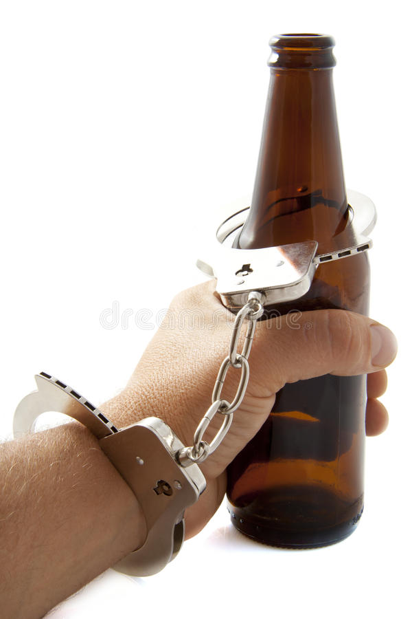 Addiction. Hand with handcuffs and bottle of beer royalty free stock images
