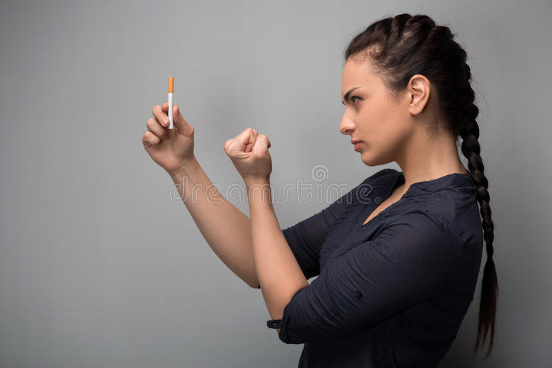 Addiction. Closeup of young woman determined girl. Closeup of young attractive Caucasian woman determined girl holding cigarette showing fist. Quit smoking stock photos