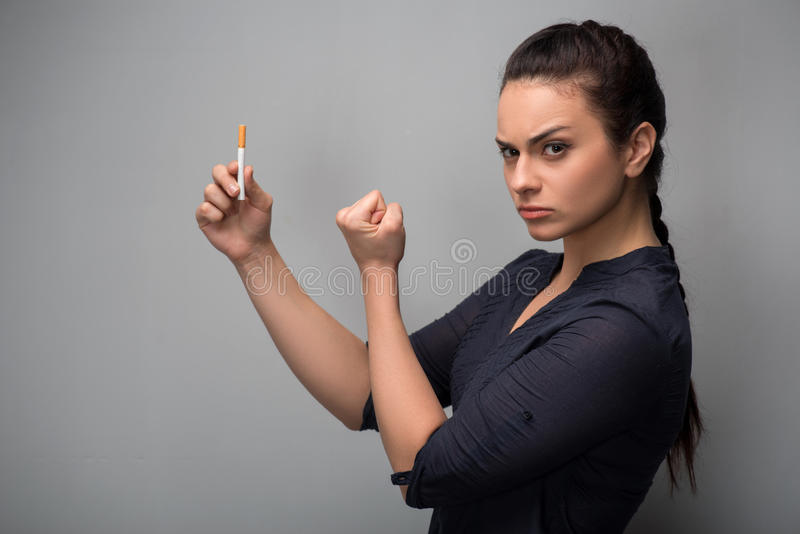Addiction. Closeup of young woman determined girl. Closeup of young attractive Caucasian woman determined girl holding cigarette showing fist. Quit smoking stock photography
