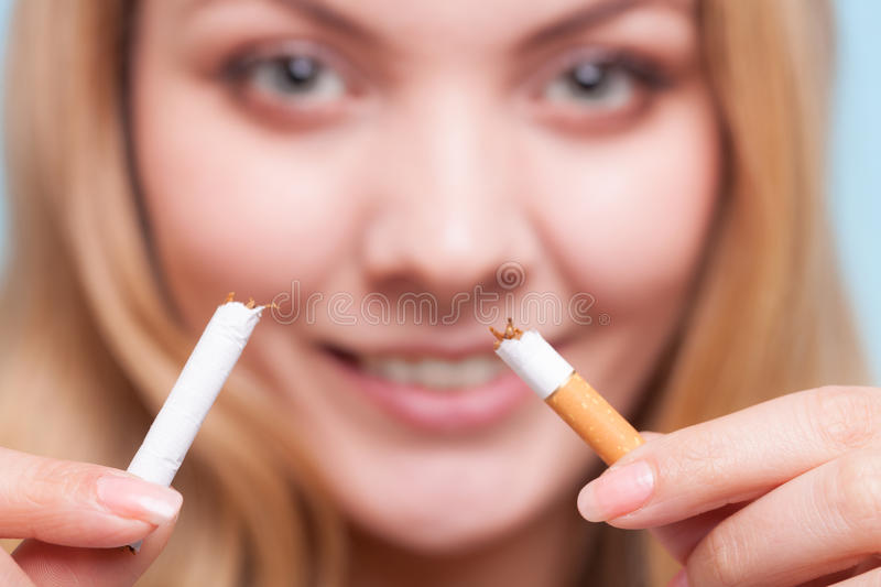 Addiction. Girl breaking cigarette. Quit smoking. Addiction. Closeup of young woman determined girl breaking the cigarette. Quit smoking. Studio shot royalty free stock images