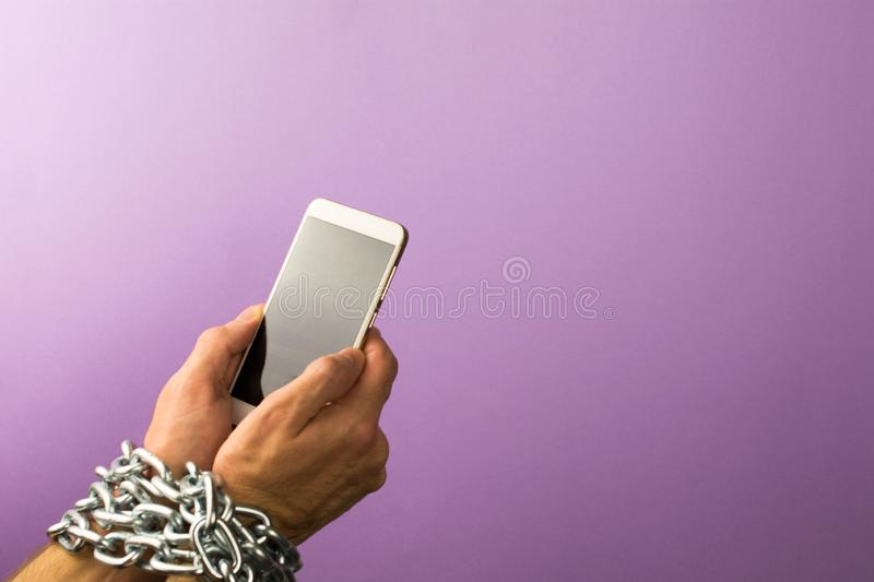 Addiction to smartphone or mobile devices concept. Mobile phone chained to the hands of a man.  Addiction to smartphone or mobile devices concept stock photos