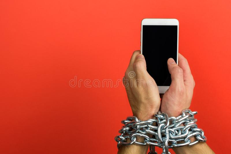 Addiction to smartphone or mobile devices. Hand is tied with a chain to the smartphone. Addiction to smartphone or mobile devices concept royalty free stock photo