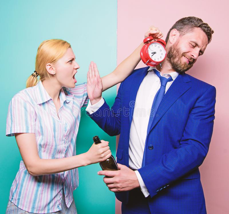 Addictive alcoholism or alcohol abuse. Man suffering from alcoholism. Angry wife meeting drunk husband late at home. Businessman with alcohol bottle and women royalty free stock image