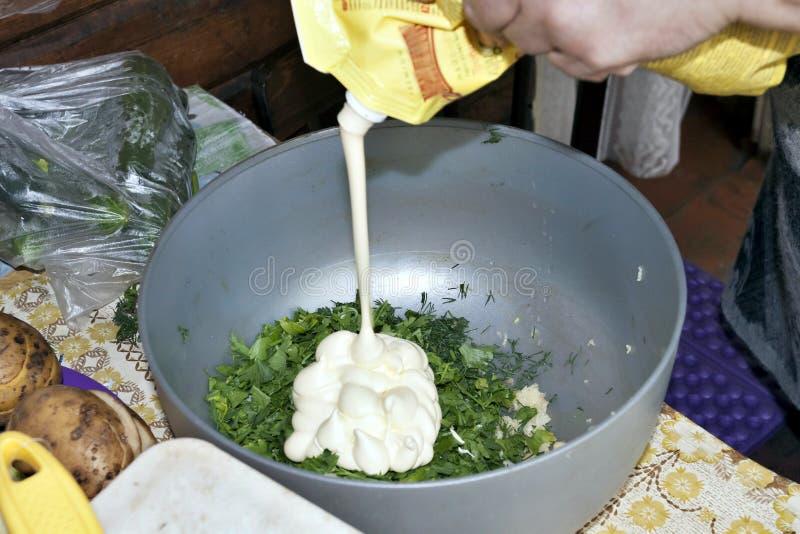 Addieren der Majonäse, um eine scharfe Soße des Knoblauchs und der Kräuter zuzubereiten lizenzfreie stockbilder