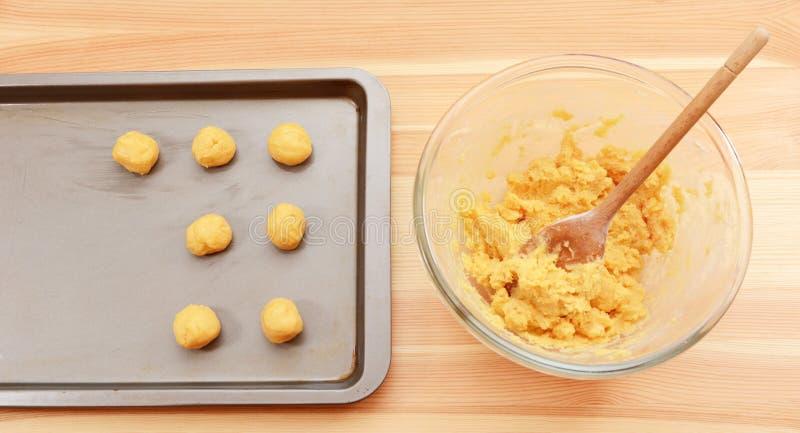 Adding balls of cookie dough to a baking sheet stock photo