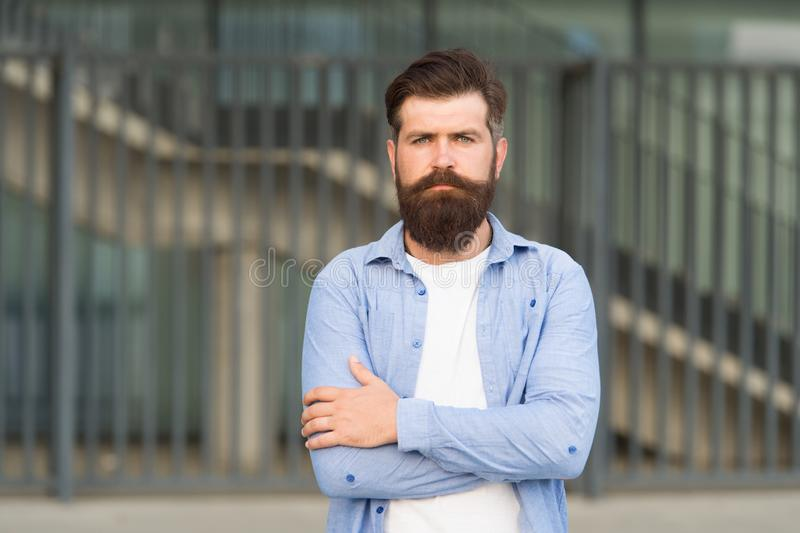 Adding care to his mustache. Serious guy wearing beard and mustache on urban background. Bearded man with stylish. Mustache shape. Brutal hipster with textured stock photography