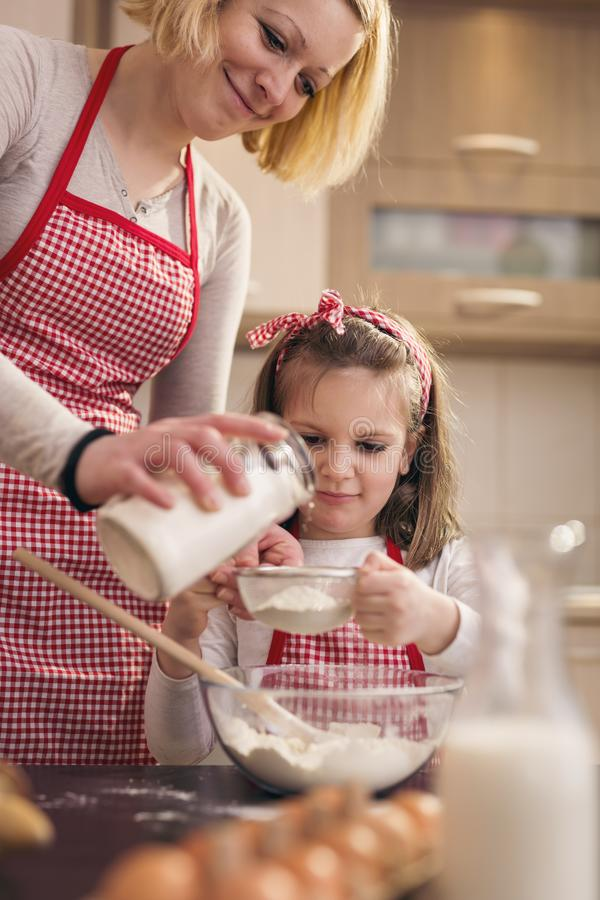 Adding flour for pizza dough kneading. Mother and daughter baking dough; mother adding more flour to the sieve while daughter sowing flour through the sieve into stock photo