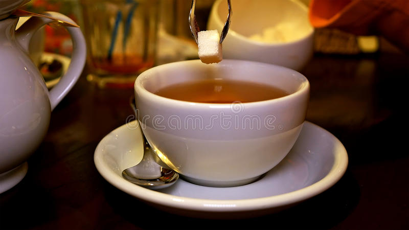 Adding lump sugar with pincers to black tea in cup. Adding sweet lump sugar with pincers tweezers to black tea cup. Tea time lunch snack breakfast dinner and royalty free stock photo