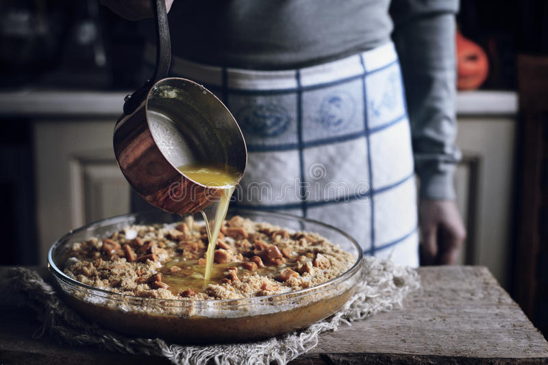 Adding melted butter in the dough for pumpkin dump cake stock images