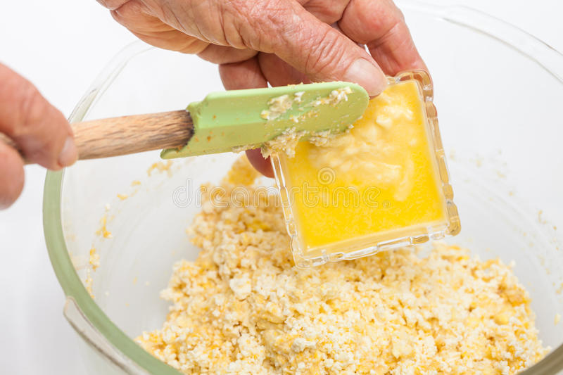 Adding melted butter to prepare sweet corn bread stock photography